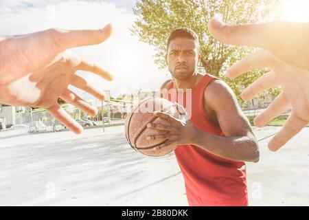 Joueur de panier multiracial jouant un jeu dans le camp urbain de quart de rue en plein air avec l'éclairage arrière - mains de l'athlète essayant de prendre le ballon de son oppo