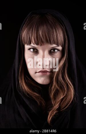 Gros plan sur la belle sorcière avec des cheveux bruns portant un châle sombre sur sa tête. Magnifique dame dans le foulard regardant l'appareil photo. Isolé sur fond noir Banque D'Images