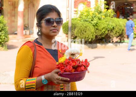 Portrait souriant de la belle jeune adulte traditionnelle mariée Bengali femme tenant un seau de l'offre religieuse des fleurs pendant Durga puja celebrati