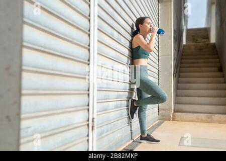 femme sportive buvant de l'eau à partir d'une bouteille après l'exercice