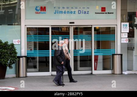 Madrid, Espagne. 19 mars 2020. Les gens se promenent à l'extérieur de l'hôpital Jimenez Diaz de Madrid, en Espagne, le 19 mars 2020, où l'ancien président régional de Madrid, Esperanza Aguirre, et le mari Fernando Ramirez, auraient vérifié pour le coronavirus. Crédit: JUANJO MARTIN/EFE/Alay Live News