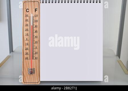 Thermomètre en bois intérieur Celsius et Fahrenheit avec calendrier de bureau vide ou bloc-notes vierge sur une étagère le jour chaud de l'été, maquette et modèle Banque D'Images