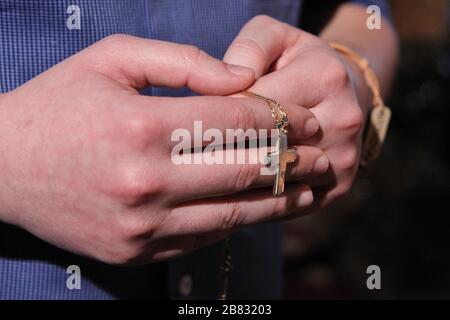 les mains de l'homme prient en tenant un rosaire de perles Banque D'Images