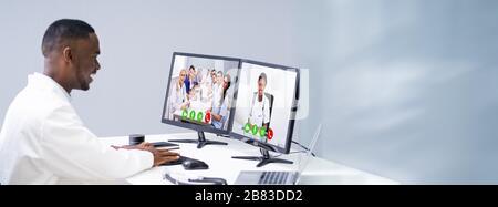 Jeune homme médecin vidéo-conférence avec l'équipe médicale sur bureau informatique en clinique Banque D'Images