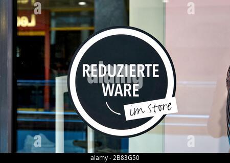 Grandes réductions en lettres allemandes sur un signe dans la fenêtre de boutique. Banque D'Images