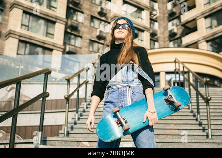 Jeune femme caucasienne se posant dans la rue avec planche à roulettes dans les mains. Jeune fille en jeans bleu sports extrêmes dans un environnement urbain. Thème de la jeunesse