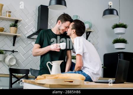 Un couple gay heureux prenant le petit déjeuner dans la cuisine et utilisant un ordinateur portable. Les hommes homosexuels pleins de plaisir se embrassent, font face à face tout en passant du temps à la maison. Banque D'Images