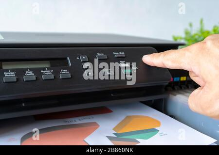Doigts qui pressent le bouton, l'imprimante est entièrement fonctionnelle, située sur le bureau. Il est important au bureau de présenter le travail et le succès Banque D'Images