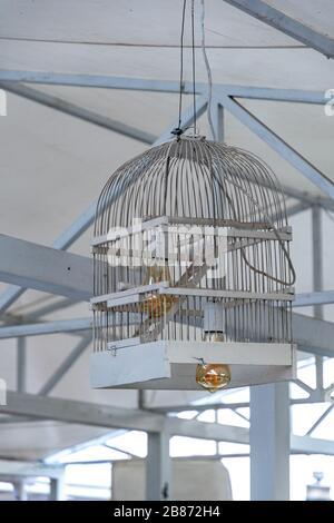 Abat-jour en cage d'oiseaux en bois peint blanc. Gros plan de cage à oiseaux transformé en plafonnier avec ampoule en verre de couleur dorée à l'intérieur. Banque D'Images