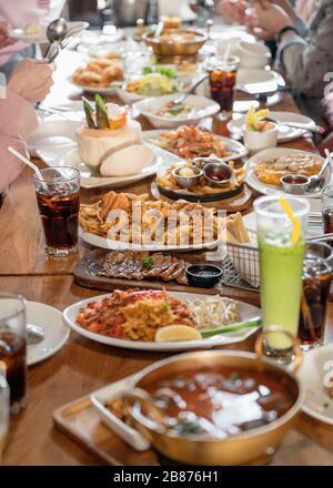 Divers types de plats gastronomiques et de boissons avec repas en famille sur table en bois au restaurant