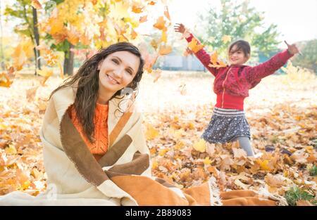 Jolie jeune mère joyeuse transformée en plaid et assise sur une pelouse avec des feuilles jaunes d'automne sur le fond de sa petite fille et gaie fr Banque D'Images
