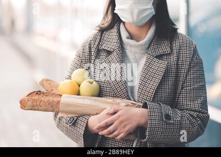 Jeune femme tenant des aliments marchant dans la rue portant un masque médical à l'extérieur. Distanciation sociale. Concept de virus.