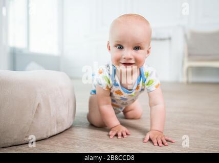 Portrait d'un bébé joyeux rampant sur le sol. Le concept d'un enfant développé en bonne santé. Préparation des premières étapes du bébé Banque D'Images