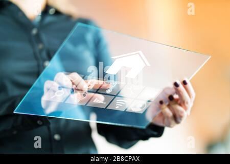 Femme utilisant une application de contrôle intelligente à domicile avec une tablette en verre transparent futuriste. Appuyez sur le bouton pour contrôler la propriété.