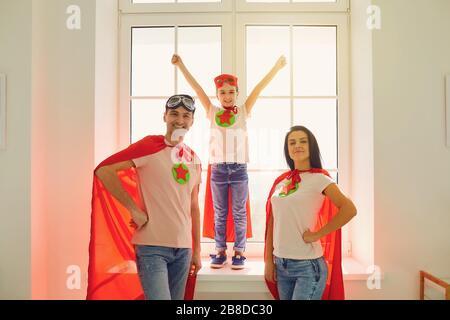 Une famille joyeuse en costume de super héros riant tout en se tenant sur le fond d'une fenêtre dans une salle à l'intérieur.