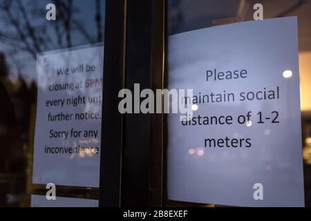 Un panneau d'avis de santé devant un magasin mandate des mesures de distanciation sociale en réponse à la pandémie de Coronavirus. Banque D'Images