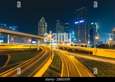 Longue exposition de voitures qui passent sur la route la nuit devant les gratte-ciel Dubaï - Emirats Arabes Unis