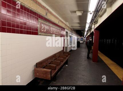 New York City, New York, États-Unis. 21 mars 2020. Un passager solitaire portant un masque attend le train numéro 1 à la gare de la 23ème rue dans le quartier Chelsea de Manhattan le samedi soir, le 21 mars 2020. Les New Yorker's de grand et de grand ont pris l'avertissement de rester à la maison à la lumière de la pandémie de coronavirus. Crédit: Adam Stoltman/Alay Live News