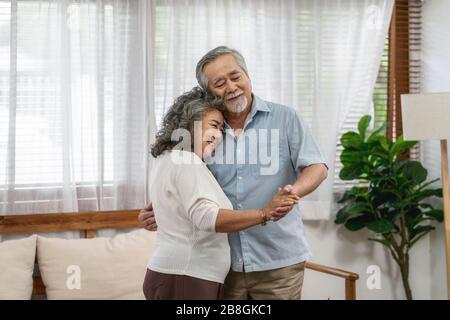 Couple asiatique Grand-parent dansant et embrassant avec un sentiment heureux dans la maison, romantique et amant avec la Valentin ou anniversaire, long live et eld