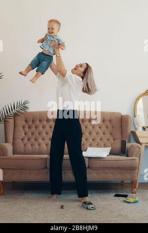 Jeune mère avec son enfant à la maison. Maman d'affaires prend une pause. Multi-tâches, freelance et concept de la maternité
