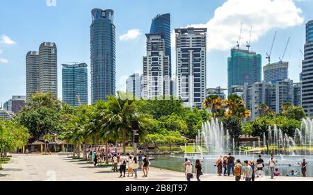 Bureaux et résidences tours et fontaines dans le lac Symphony et les touristes qui aiment passer une journée au parc KLCC Kuala Lumpur en Malaisie.