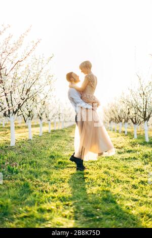 Romantique jeune homme portant sa femme dans ses bras regardant dans ses yeux avec un sourire affectueux, tout en se tenant dehors sur l'herbe verte dans beau Banque D'Images