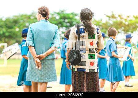 Une enseignante asiatique est en mesure de contrôler les élèves qui jouent de la musique tout en s'alignant pour payer le drapeau national le matin à l'école. Banque D'Images