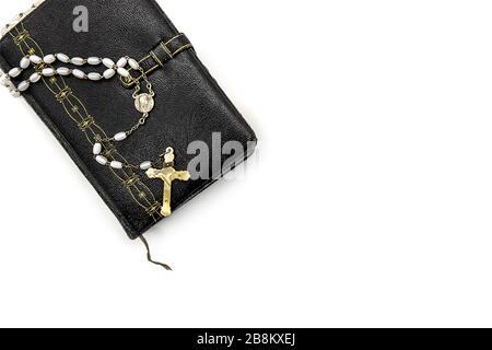 livre de prières ancien, décoré avec des ornements dorés et un rosaire avec des perles blanches et une croix ivoire Banque D'Images