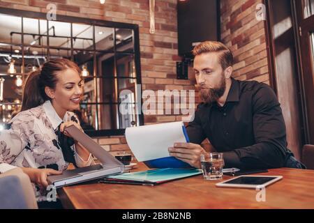 Les jeunes gens d'affaires travaillant ensemble sur le travail papier et en parlant de rapports et de finances. Portrait d'un jeune homme d'affaires et d'une femme assis dans le café A. Banque D'Images