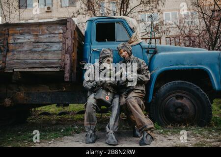 Couple amoureux se trouve dans des combinaisons de protection NBC et un masque à gaz près d'un vieux camion. Concept de mesures préventives et de protection contre le coronavirus COVID 19 pand