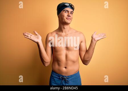 Jeune homme sans chirless portant un maillot de bain et un bonnet de bain sur fond jaune isolé sans indice et l'expression confuse avec les bras et les mains soulevées Banque D'Images