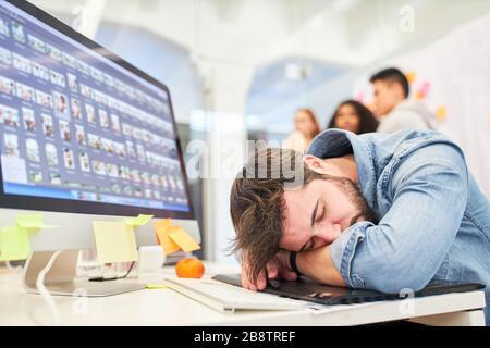 Le graphiste dort épuisé devant le moniteur PC en raison de surcharge et d'heures supplémentaires Banque D'Images