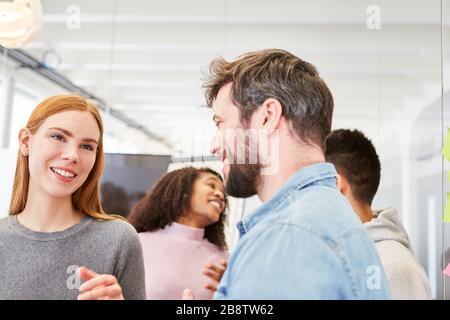 Jeunes étudiants ou collègues ayant un petit discours ou une petite réunion au bureau Banque D'Images