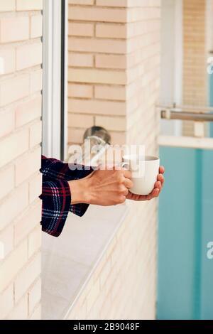 gros plan d'un jeune homme caucasien, en pyjama, ayant un café penchant sur la rampe d'une fenêtre, à sa maison ou à un hôtel