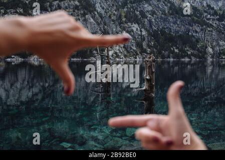 Les mains de femme non focalisées encadrent certains arbres dans un paysage de montagne.