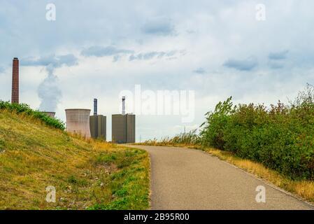 Vue sur les prés, les allées et les buissons d'une centrale électrique avec tour de refroidissement vapeur à l'horizon Banque D'Images