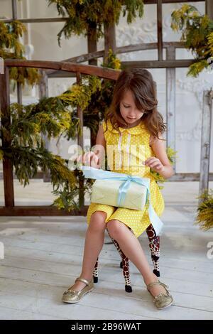 Bonne petite fille, adorable tout-petit dans une robe jaune, tenant un cadeau d'anniversaire, boîte ouverte décorée d'un noeud, excitée et surprise
