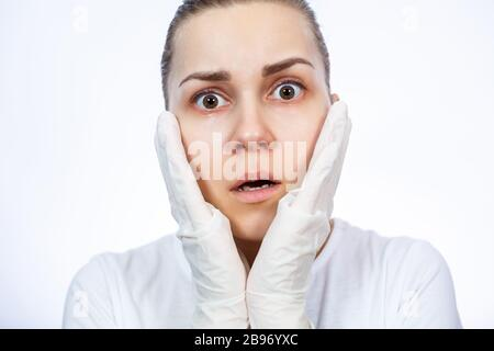 Fille paramédic met des gants médicaux blancs sur les mains. Protection contre les germes et les virus. Elle est dans un T-shirt blanc sur un fond blanc. Banque D'Images