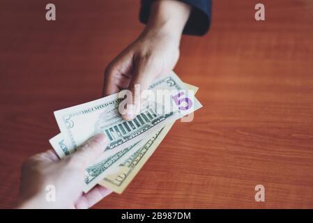Homme d'affaires donner de l'argent pot concept / personne mains homme donnant de l'argent sur le fond de table en bois payer de l'argent à la livraison payer pour recevoir de l'argent