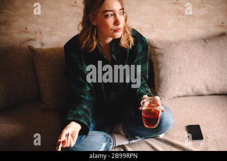 Jeune femme réfléchie qui tient une tasse de thé et de chocolat tout en étant assise sur un canapé à la maison