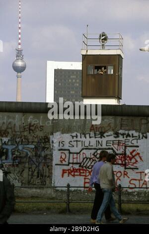 Les gens marchent devant le mur de Berlin peint par des graffitis à Berlin. Derrière elle, sur le côté est de Berlin, vous pouvez voir la tour de télévision et un garde-frontière dans la fenêtre d'une tour de guet. [traduction automatique] Banque D'Images