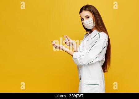 Une jeune femme médecin dans un manteau blanc et un masque de protection met un désinfectant sur ses mains. La jeune femme en uniforme médical met l'antiseptique sur les mains Banque D'Images