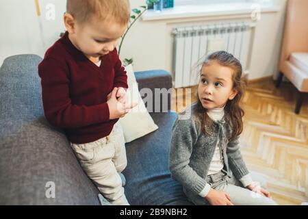 Jolie fille caucasienne assise sur le canapé avec son frère tout en passant du temps ensemble Banque D'Images