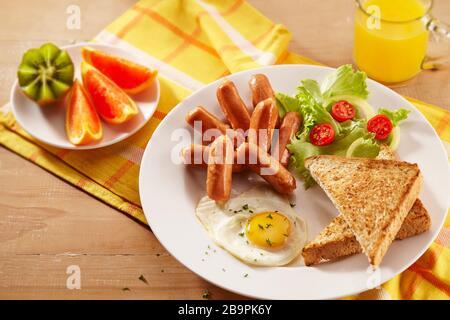 Une assiette de petit-déjeuner contenant des saucisses à cocktails, du pain grillé, des œufs frits, des salades, des fruits et un verre de jus d'orange Banque D'Images