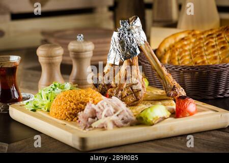 Porte-fruits de côtelettes de piment de bœuf épicé avec un poivre de Cayenne grillé et des tomates servis sur une planche à découper en bois ancienne et vue rapprochée Banque D'Images