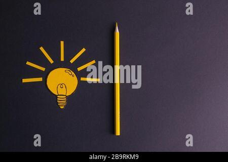 Un crayon jaune à côté d'une ampoule peinte. Le concept d'innovation et d'idées créatives Banque D'Images