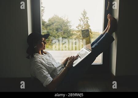 Fille hipster élégante avec ordinateur portable assis au sol à grande fenêtre avec vue sur les bois. Jeune femme heureuse en chapeau en utilisant un ordinateur portable, des achats ou de travail onlin