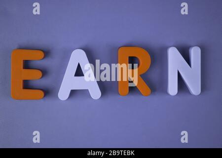 Gagnez un mot écrit avec différents blocs de lettres de couleur disposés sur un fond bleu clair