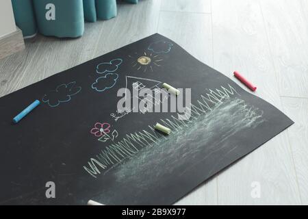 Peintures pour enfants sur papier noir. Dessin de maison Banque D'Images