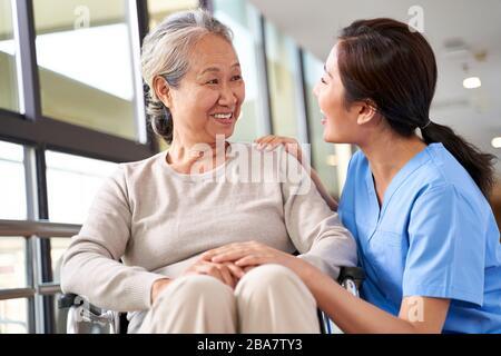 personnel soignant sympathique de la maison de soins parlant à la femme asiatique senior dans le couloir Banque D'Images